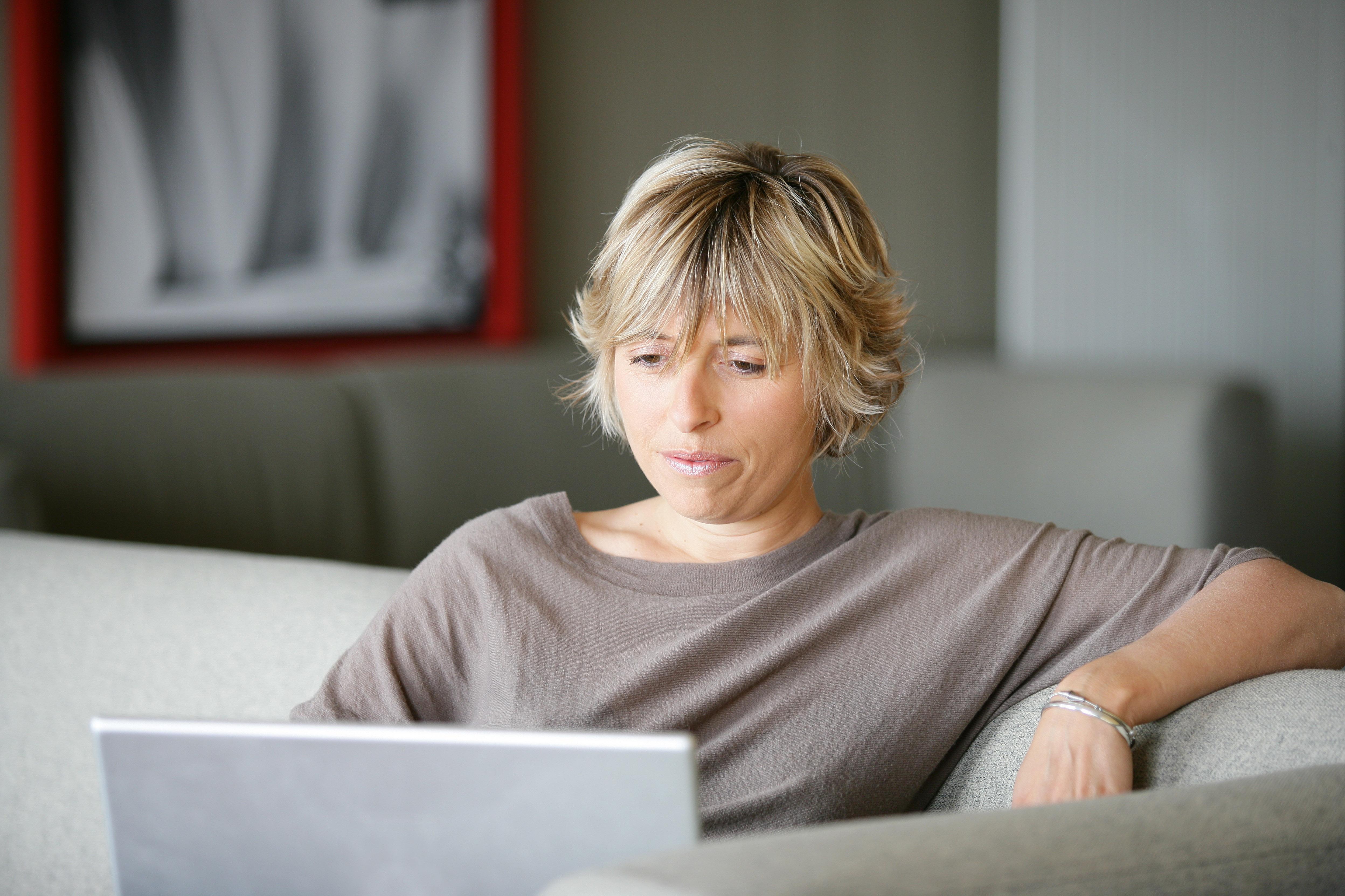 Kvinde tjekker mail i sofa