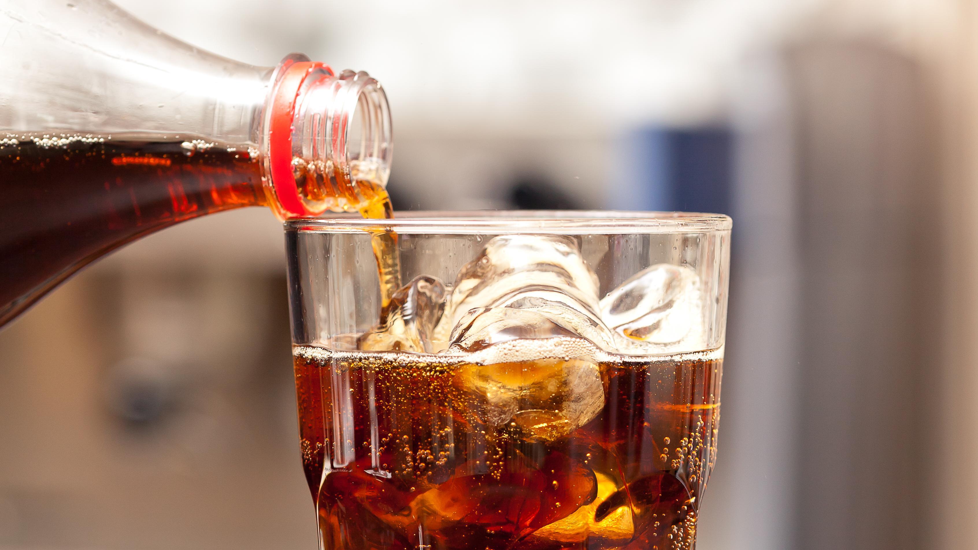 Colaflaske hælder op i glas