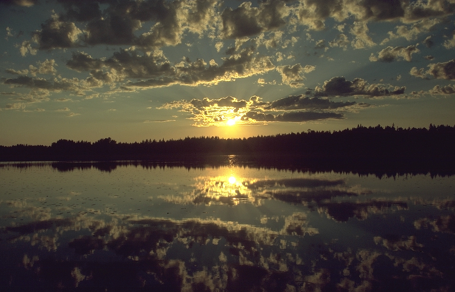 sunset_over_forest_and_lake_north_sweden_july_2005.jpg